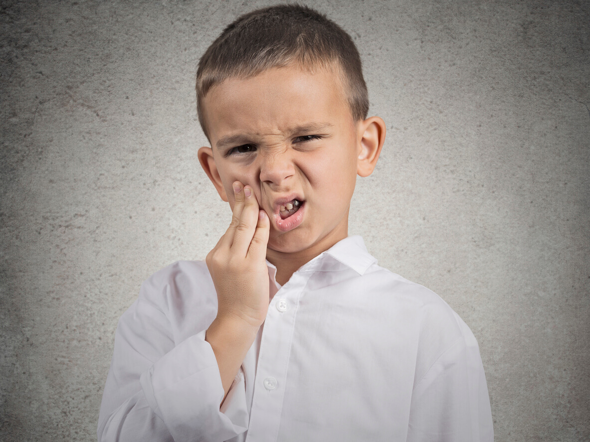 Male child holding side of mouth indicating a toothache.