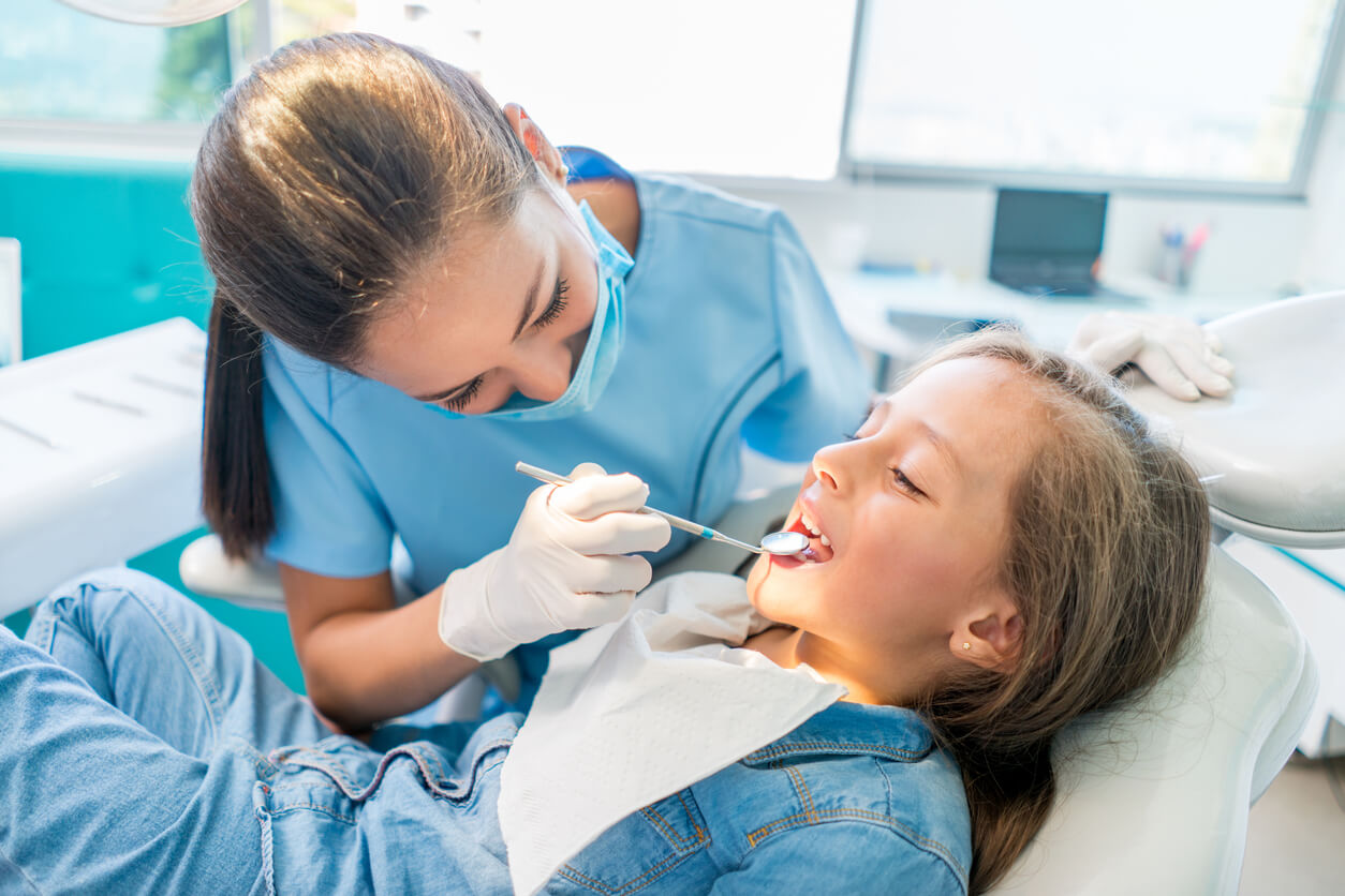 Young girl sitting in the dentist chair with a woman dentist examining her teeth.
