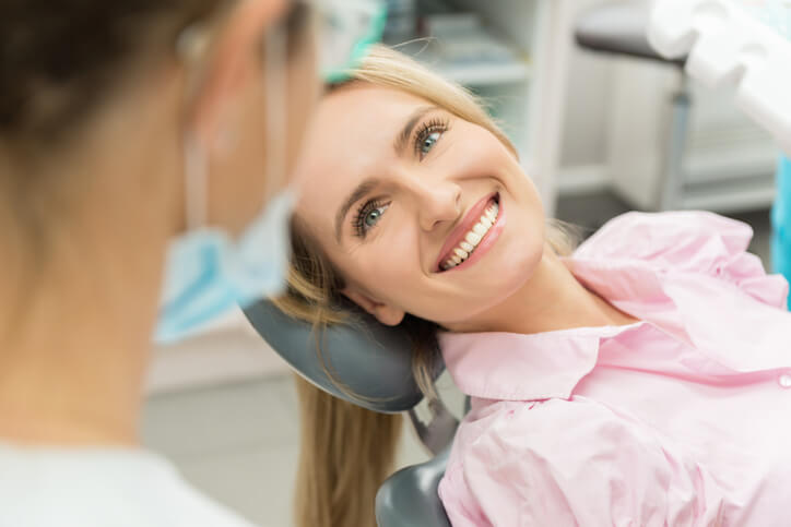 Woman laying in dentist chair smiling and looking up at dentist