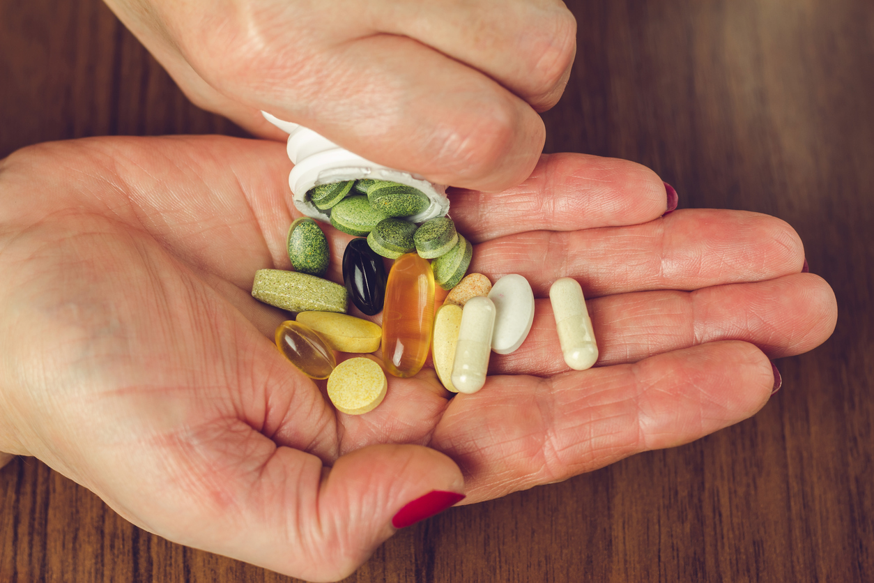 Palm of hand with a variety of vitamins being poured into it.