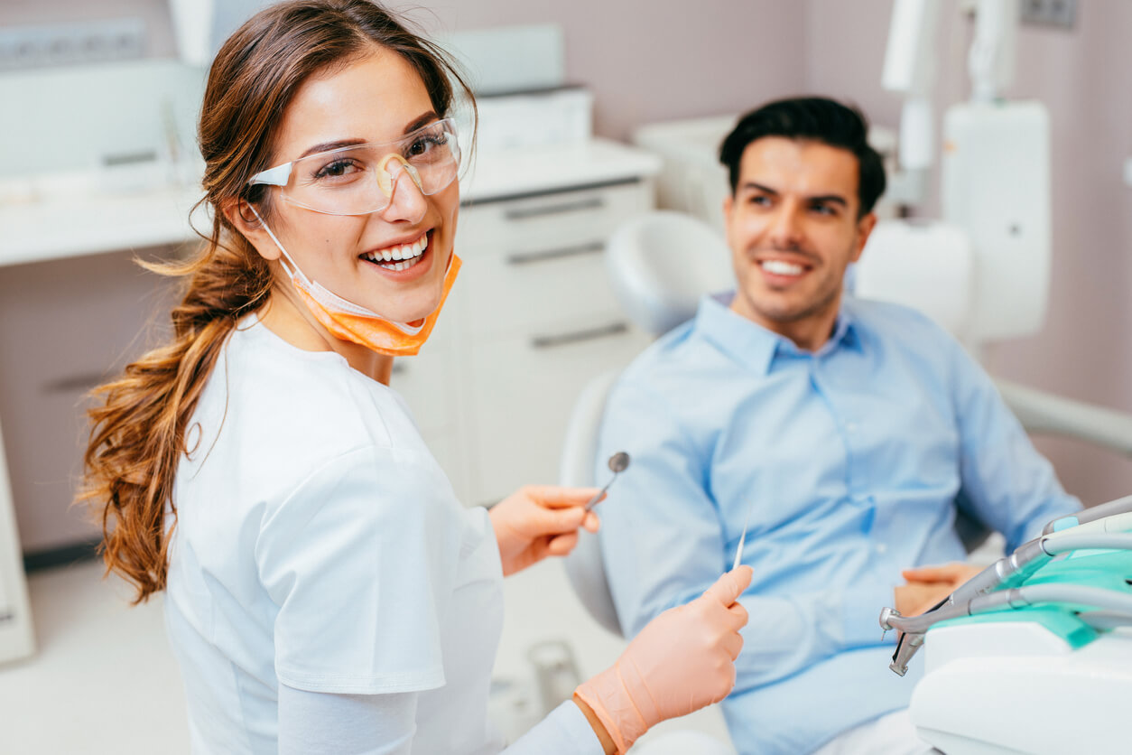 Woman dentist smiling at camera with male patient in the dentist chair