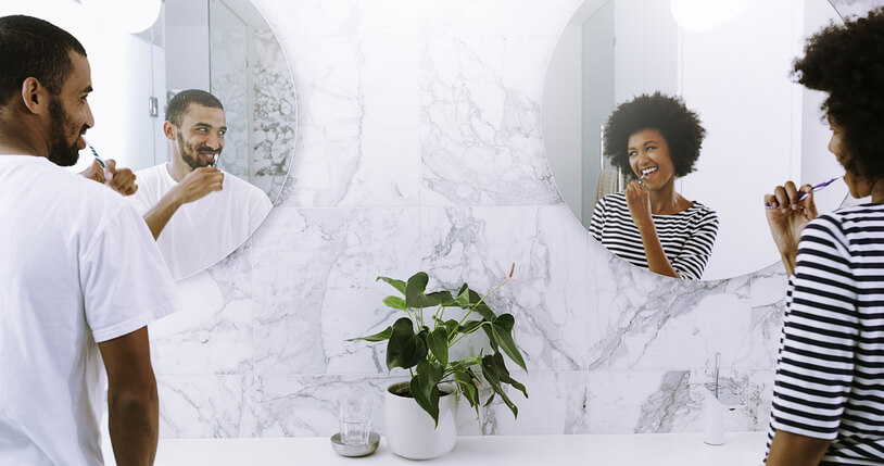 African American male on the left and female on the right brushing their teeth in the mirror and smiling looking at each other.